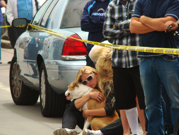 A woman clutches her dog in shock and sadness.