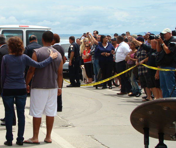 Friends, family and fans watch in complete stillness as the body is taken away.