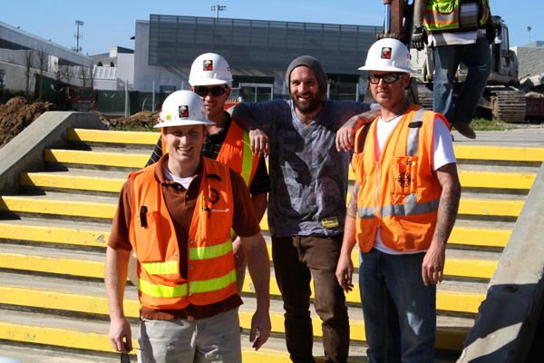 Kris Markovich poses with construction workers.